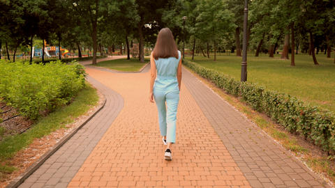back view cheerful caucasian woman walking have fun on the street in city park Live Action