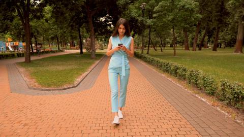 slim businesswoman using smartphone typing message in blue elegant suit walks on pedestrian zone Live Action