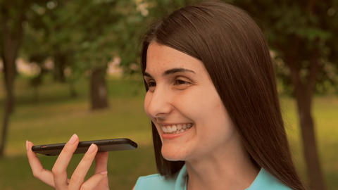 close up face cheerful young woman speak send sound message by mobile outdoors Live Action