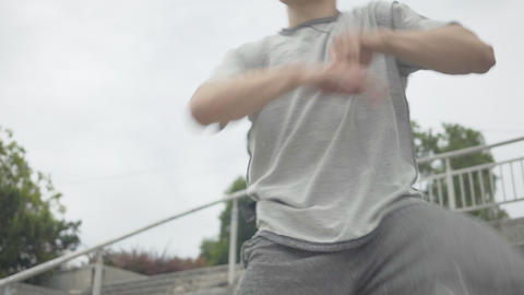 Camera zooming out from active young man moving to group of cheerful young Live Action