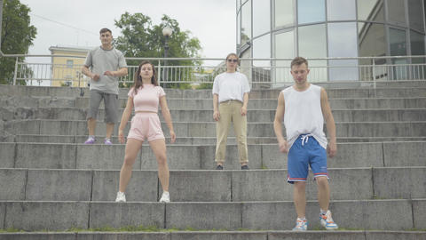 Wide shot of four Caucasian people dancing on urban stairs in urban city Live Action