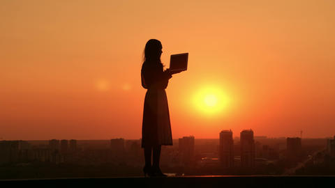 woman with computer outdoors cityscape at sunrise Live Action