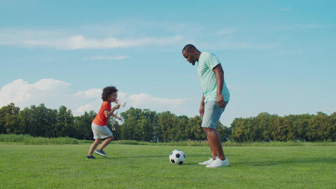 Little football trainer coaching father outdoors Live Action