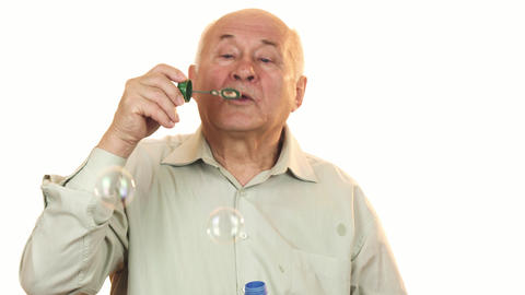 Senior cheerful man blowing bubbles isolated on white Live Action