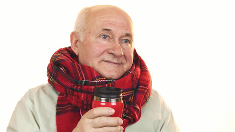 Cheerful senior man wearing a scarf holding thermos smiling happily Live Action