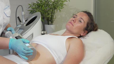 Mature woman enjoying endospheres hardware massage at beauty clinic Live Action