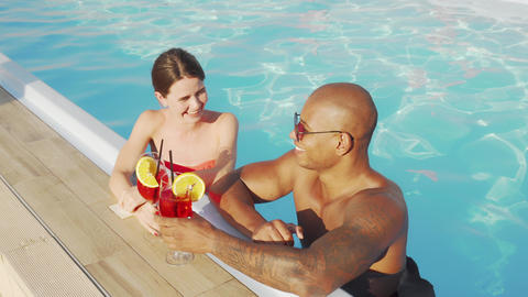 Happy multiethnic couple clinking glasses in the swimming pool Live Action