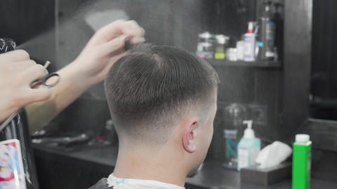 Professional barber wetting and combing hair of a male client Live Action