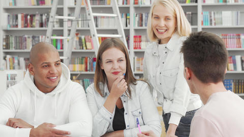 Cheerful young people enjoying talking at the college library after studying Live Action