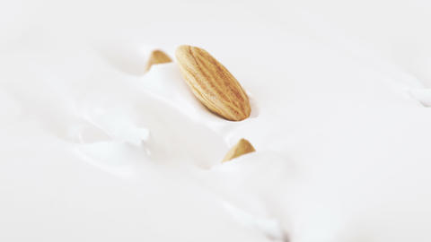 Almonds Nuts Falling Into Liquid Yogurt in 4K Super slow motion Live Action