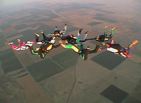 Eleven skydivers free fall in formation and disperse Stock Video Footage