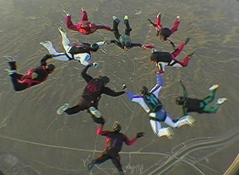 Ten skydivers free fall in formation and disperse Stock Video Footage