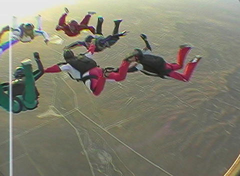 Ten skydivers free fall in formation and disperse Footage