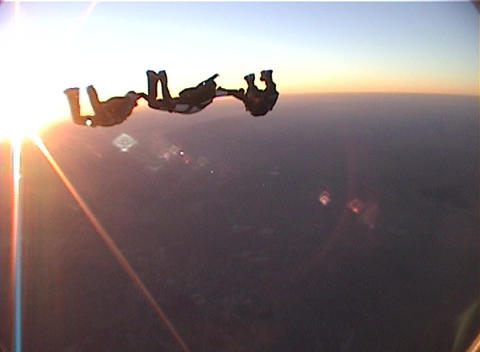 Skydivers freefall and form a design by clasping hands in... Stock Video Footage