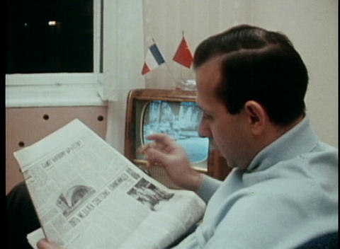 A dated shot of a man reading a newspaper, smoking a... Stock Video Footage