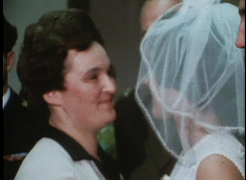 A couple gets married and the bride and groom kiss in an archival home movie style shot Footage