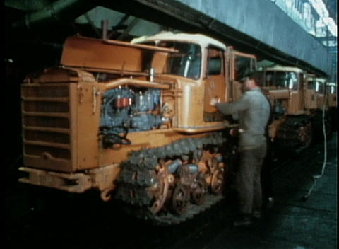 Workers build tractors and trucks in a factory in this... Stock Video Footage