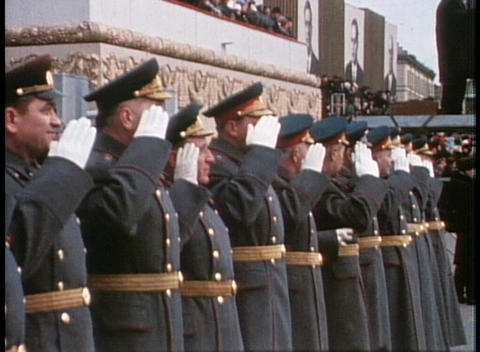 An old poster of a Soviet leader looks down upon a military parade Footage