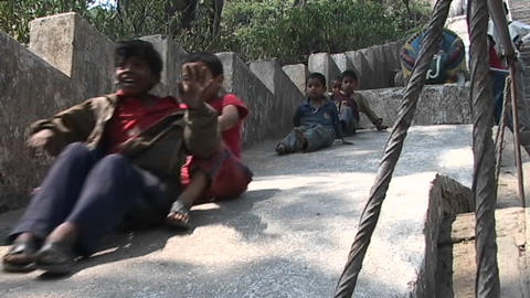 Nepal children playing and smiling while sliding down a cement slope in Kathmandu Footage