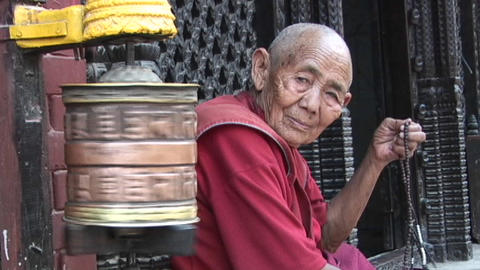 Old Buddhist monk (or nun) with prayer beads next to spinning prayer wheel in Kathmandu Footage