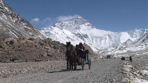 Tibetan men and climber riding in a carriage pulled by horse near base camp with Mt. Everest in the Footage