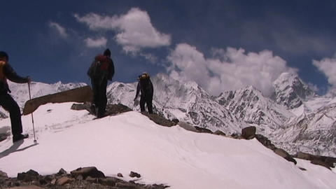 Climbers near Mt. Everest in Tibet walking over a snow hill with Mt. Pumori in the background Footage