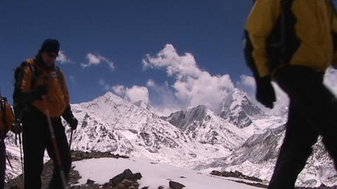 Climbers walking towards Mt. Everest base camp in Tibet with Mt. Pumori and the mountains of Nepal i Footage