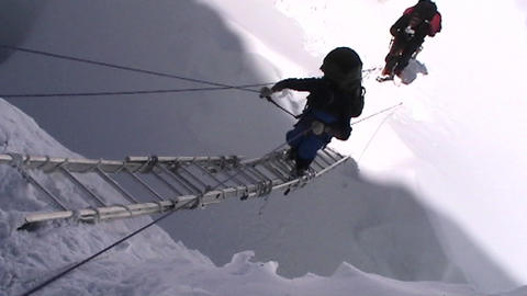Climber climbs up ladders on Mt. Everest Footage