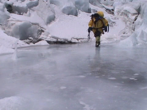 Climber walks across a path of mountain ice Stock Video Footage