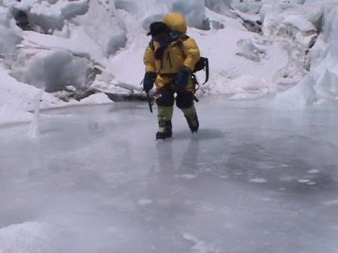 Climber walks across a path of mountain ice Stock Video Footage