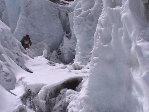 Climber walks across an ice field of ice seracs Stock Video Footage