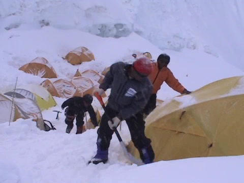 A climber digging out snow from around his tent Stock Video Footage