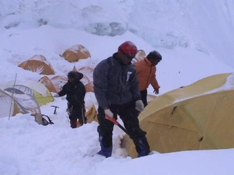 A climber digging out snow from around his tent Footage