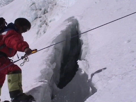 A Climber walking over a small crevasse on Mt. Everest Stock Video Footage