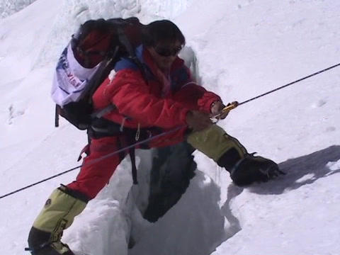 A Climber walking over a small crevasse on Mt. Everest Footage
