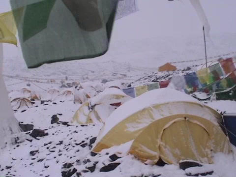 Snow falling on a tent with prayer flags blowing in the wind Footage