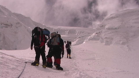 A team of climbers ascends an icy slope on Mt. Everest as clouds roll across the sky above Footage