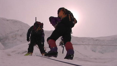 The sun beats down on climbers as they ascend icy slope Footage
