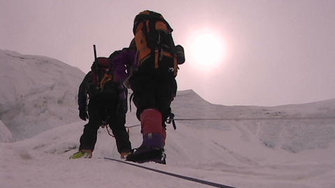 The sun beats down on climbers as they ascend icy slope Stock Video Footage