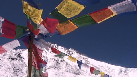 Buddhist prayer flags blowing in the wind as the summit of Mt. Everest looms in the background Footage