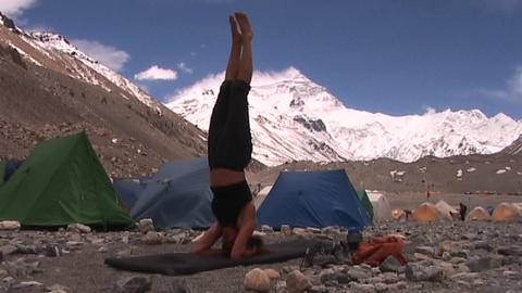 Attractive woman does yoga headstand at Mt. Everest base... Stock Video Footage