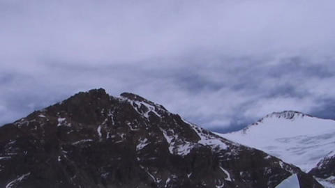Time lapse of clouds moving over two summit peaks near... Stock Video Footage