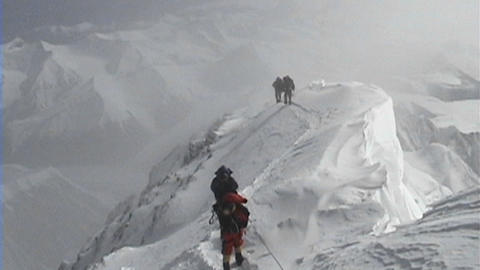 Climbers coming down from the summit of Everest climbing over an extremely exposed area Footage