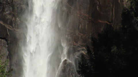 The camera pans up through thick vegetation to the top of a steep waterfall Footage