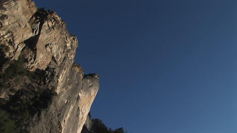 The camera pans left across vertical cliffs to a... Stock Video Footage