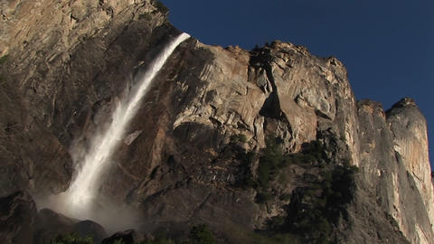 The camera pans left across vertical cliffs to a cascading waterfall Footage