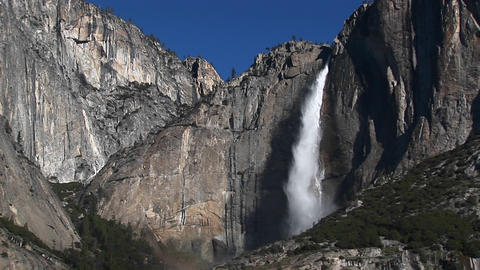 Steep, rocky mountains feature a spectacular waterfall... Stock Video Footage