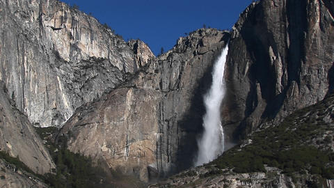 Steep, rocky mountains feature a spectacular waterfall and spray as it plummets to the bottom Footage