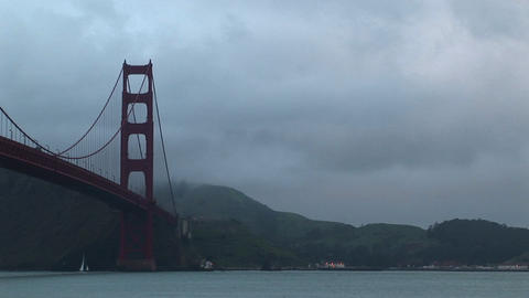 The stark, geometric shapes of the Golden Gate Bridge contrasts with natural beauty of fog on San Fr Footage