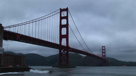 Surf rolls over rocks under historic Golden Gate Bridge... Stock Video Footage